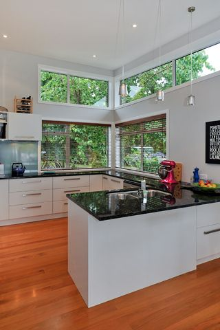 Family kitchen with loads of natural light coming through the high level windows. The natural timber floors work well with the white cabinets and grey granite