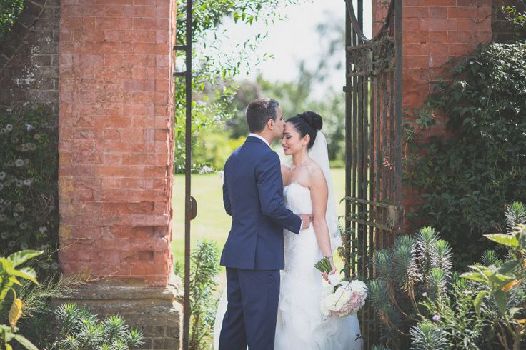 Stealing a kiss at Barnett Hill; a country house wedding venue near Guildford, Surrey.
