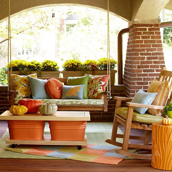 Colorful Fall Porch  -  Take a color scheme through the season with pretty, inexpensive fall accents. Outdoor pillows add pick-me-up to a porch swing while a small throw rug keeps the palette going. Make a simple table by sandwiching two colorful tubs between slabs of wood. We added wheels to the base board to make it mobile.