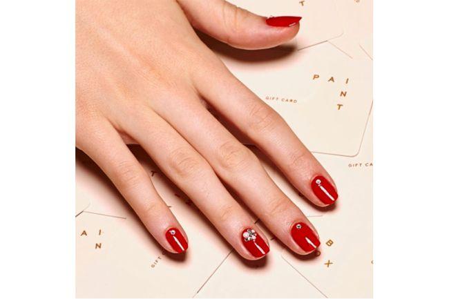 Roter Nagellack Maniküre mit Glitzersteinen