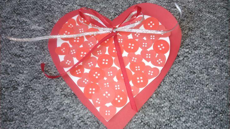 Papírové srdce s papírovými knoflíky a stuhou.