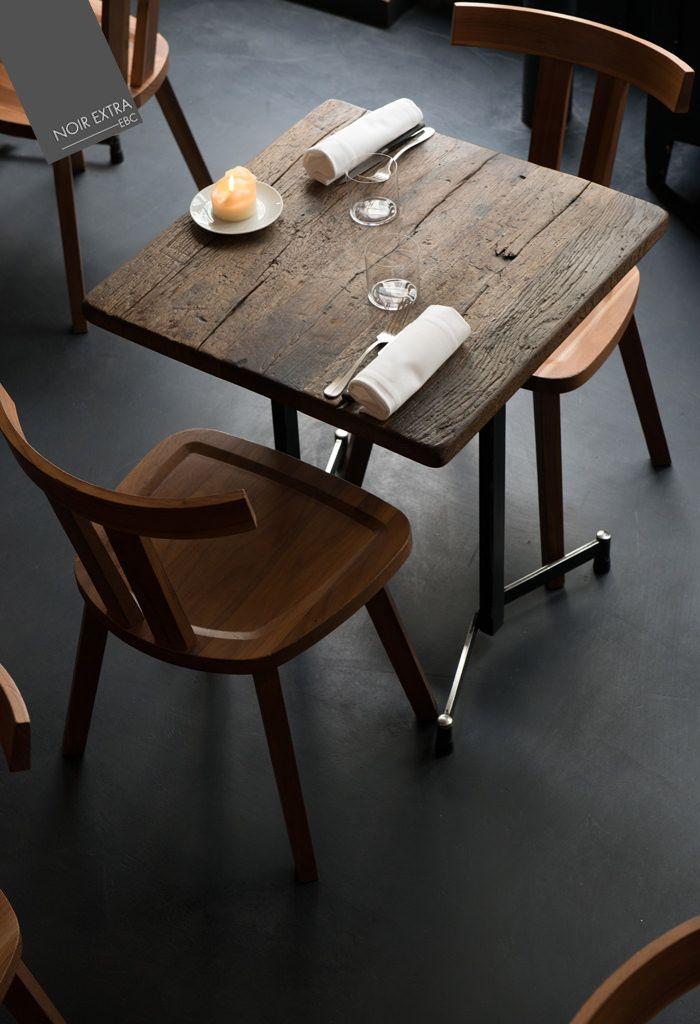 Gros plan sur le sol en ENDUIT BETON COLORE, couleur Noir Extra,  dans le restaurant SEPTIME, Paris. Il met en valeur le mobilier en bois brut et contribue à une ambiance de charme, mi-indus, mi vintage.