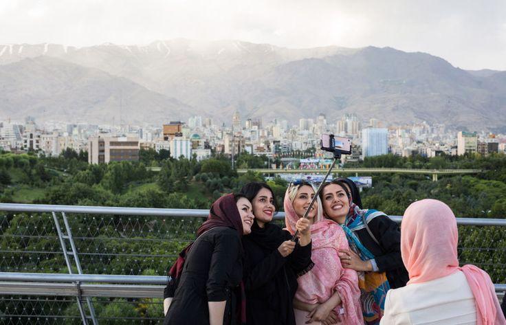 Iranische Frauen nehmen vor der Kulisse Teherans ein Selfie auf
