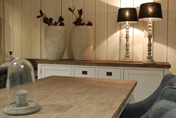 Een mooi voorbeeld van een warme en sfeervolle setting. Het witte dressoir van acaciahout is voorzien van een geolied bovenblad wat voor een mooi contrast zorgt. De accessoires in de vorm van bijpassende tafellampen met zwarte kap en stoffen eetkamerfauteuils maakt het helemaal af.