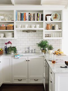 A ceramic subway-tile backsplash, sleek marble countertops, crisp white open shelving on top, and Shaker-style cabinets on bottom create a monochromatic look in this small-space kitchen in Hot Springs, Ark.