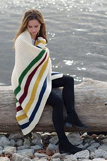 This simple to knit lap cozy is worked completely in garter stitch in a bulky wool to knit up quickly. Follow the inspiration of the Hudson's Bay Company's point blanket, or pick 5 colours of your choice.