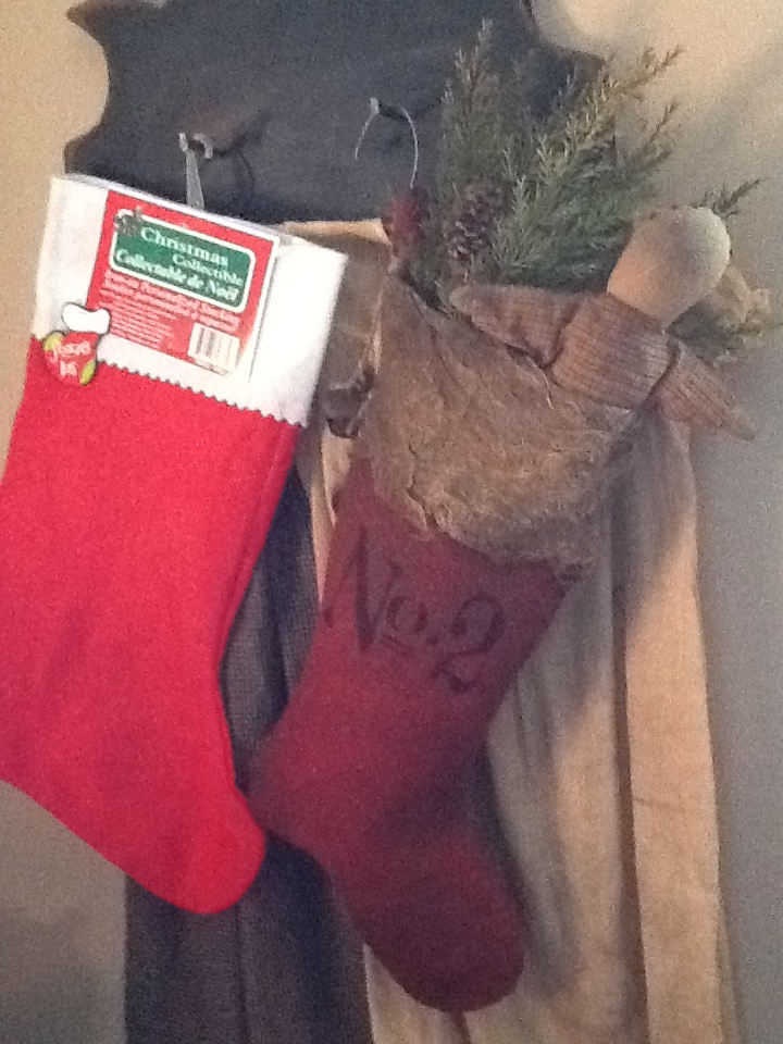 A dollar tree stocking make over. I first soaked the stocking in instant coffee and then baked it in the oven at a low temperature. Then I hit it with rustoleum's brown multi texture spray paint, going heavier on the toe and on the white trim. Next I took some coffee baked cheesecloth and spray painted that a touch with the same brown multi textuxture spray paint. Then I used spray adhesive to glue it to the top of the stocking, leaving some of the trim peeking through. Then stenciled it.
