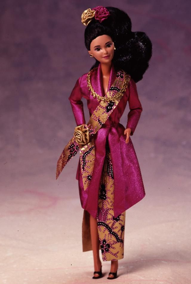Malaysian Barbie doll wears an ornate costume usually reserved for special occasions like weddings and holidays. Her colorful dress and accompanying sash represent batik, a traditional Malaysian craft of combining waxes and dyes. Her overcoat is a rich pink color, and complementing her rosy complexion. Malaysian Barbie doll's hair is pulled back and tied with colorful flowers.