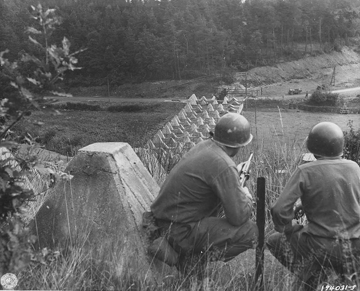 """Two US soldiers looking down a row of """"dragon's teeth"""" concrete tank obstacles on the Westwall northwestern Germany 15 September 1944."""