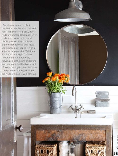 I love the simplicity of this modern rustic bathroom: a simple galvanized light, a round mirror, planked white backsplash and a beautifully distressed vanity. Inky black paint makes it more moody, less cute.