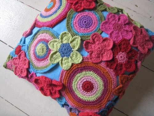 Take an inexpensive solid colored cushion and stitch fun crocheted appliques all over it. ;)