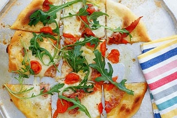 Top a homemade base with creamy mozzarella, ripe tomatoes and prosciutto, and enjoy your pizza al fresco this weekend.