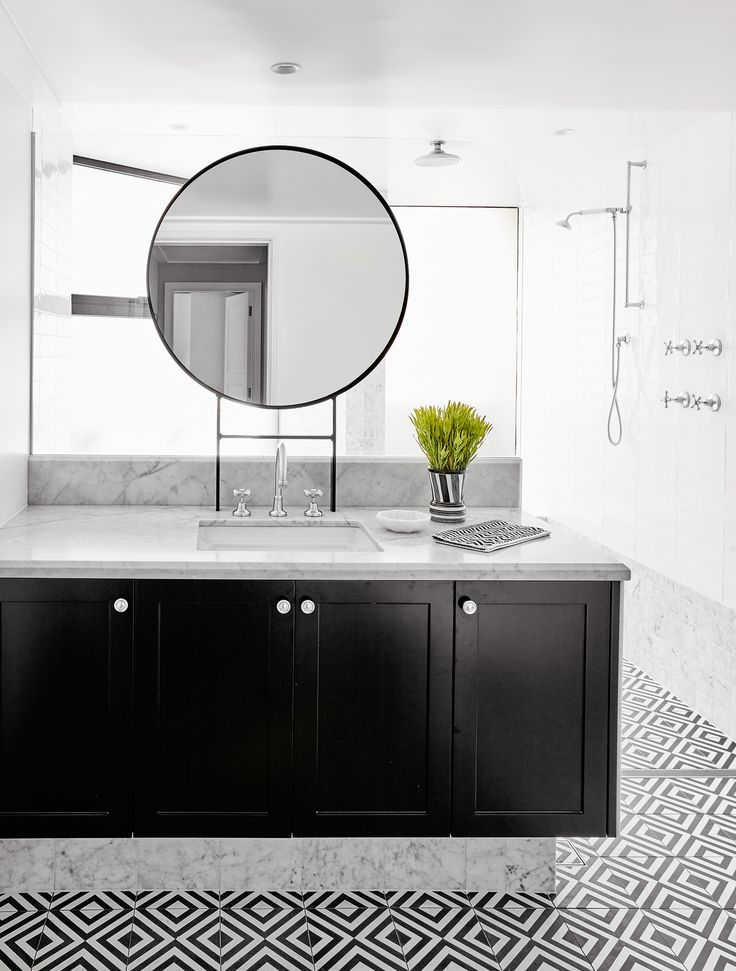 'Oxford Black' tiles by Teranova add a modern edge to this bathroom featuring marble surfaces and classic finishes. Photography: Will Horner | Story: Belle