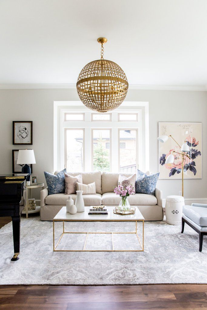 Feminine living room with a beige sofa and gold woven pendant