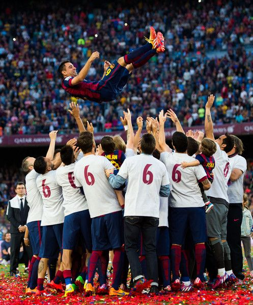 Xavi Hernandez (top) of FC Barcelona is tosed by his teammates after the La Liga match between FC Barcelona and RC Deportivo La Coruna at Camp Nou on May 23, 2015 in Barcelona, Catalonia.