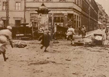 Polacy walczący w Warszawie z niemieckim najeźdźcą przebiegają przestrzeń pod niemieckim obstrzałem