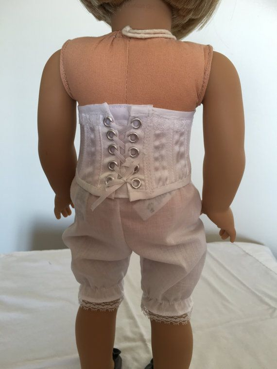 Dressing your doll historically correct starts with the under garments. This is an acual corset as made then or now. Its constructed of white satin and lining with boning in every seam. Each piece is cut with a perfect fit to my American Girl doll body. The 12 pieces are put together and top stitching added all across the garment. Lace is added to the top edge and finished clean with a matching bias trim. The center back has two sets of eyelet holes that are laced up with a white ribbon. The…
