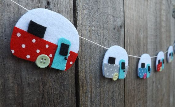 A felt caravan garland, made up of 6 retro style caravans in bright printed felt.  The van shapes are hand cut from high quality acrylic craft felt and