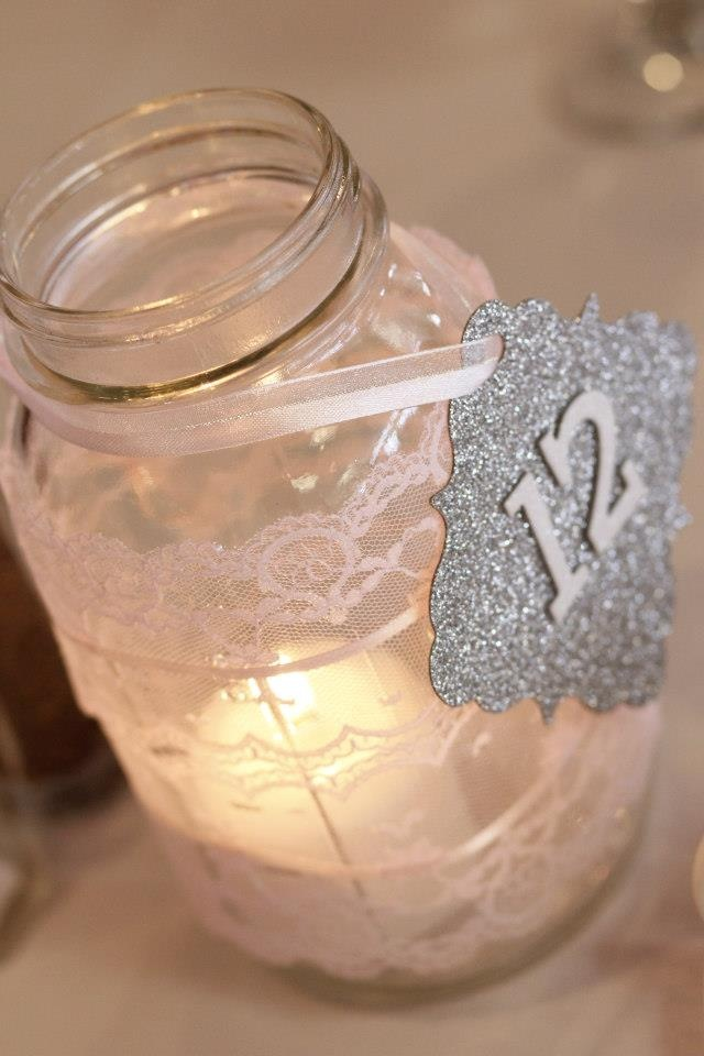 I love the glittered table number (not the mason jar for your theme).  We could do something similar in your colors and put them on stands.