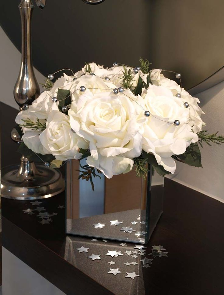 roses and silver balls in mirrored vase