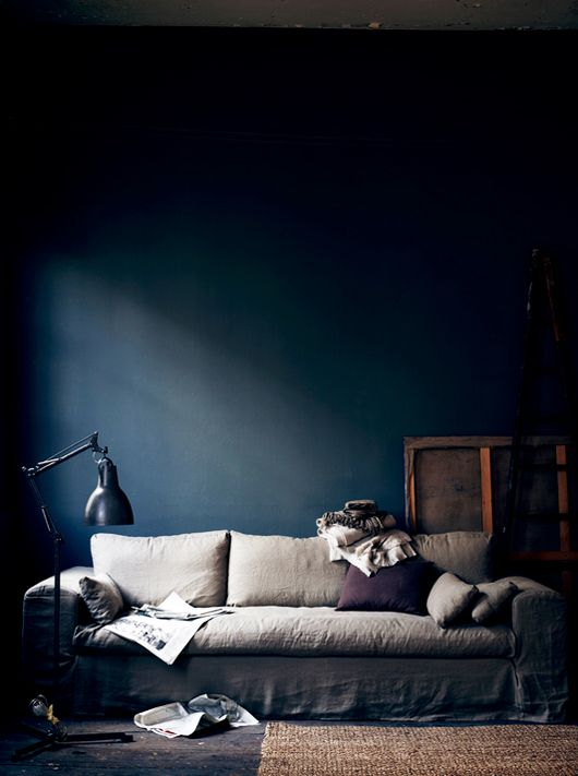 Love the mood and lighting in this room, dark walls and light linen sofa