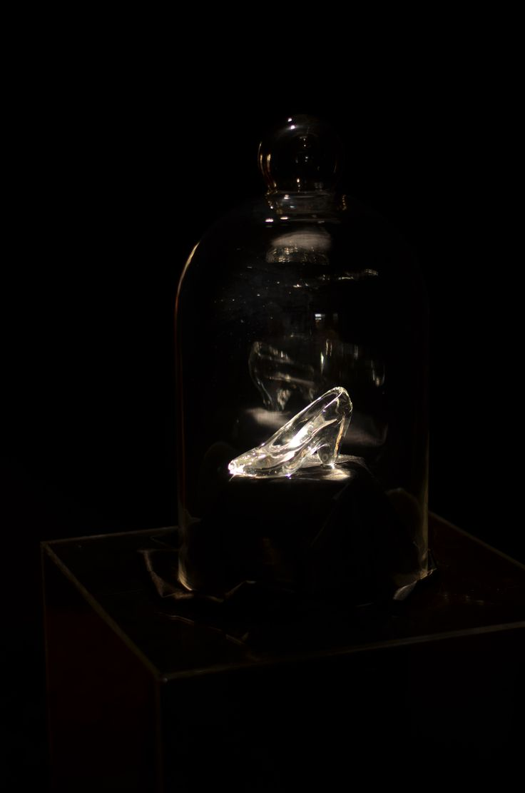 A glass slipper sat in the all black entry tunnel, lit from above it sat on an acrylic plinth under a glass cloche dome leaving the shoe glistening in the passage