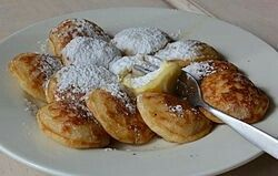 Poffertjes (Dutch pronunciation: [ˈpɔfərcəs]) are a traditional Dutch batter treat. Resembling small, fluffy pancakes, they are made with yeast and buckwheat flour. Unlike American pancakes, they have a light, spongy texture. Typically, poffertjes are served with powdered sugar and butter, and sometimes syrup or advocaat.  Mainly in the winter season, temporary stands selling poffertjes are quite popular, and sell portions containing one or two dozen of them. Usually the cook prepares them…