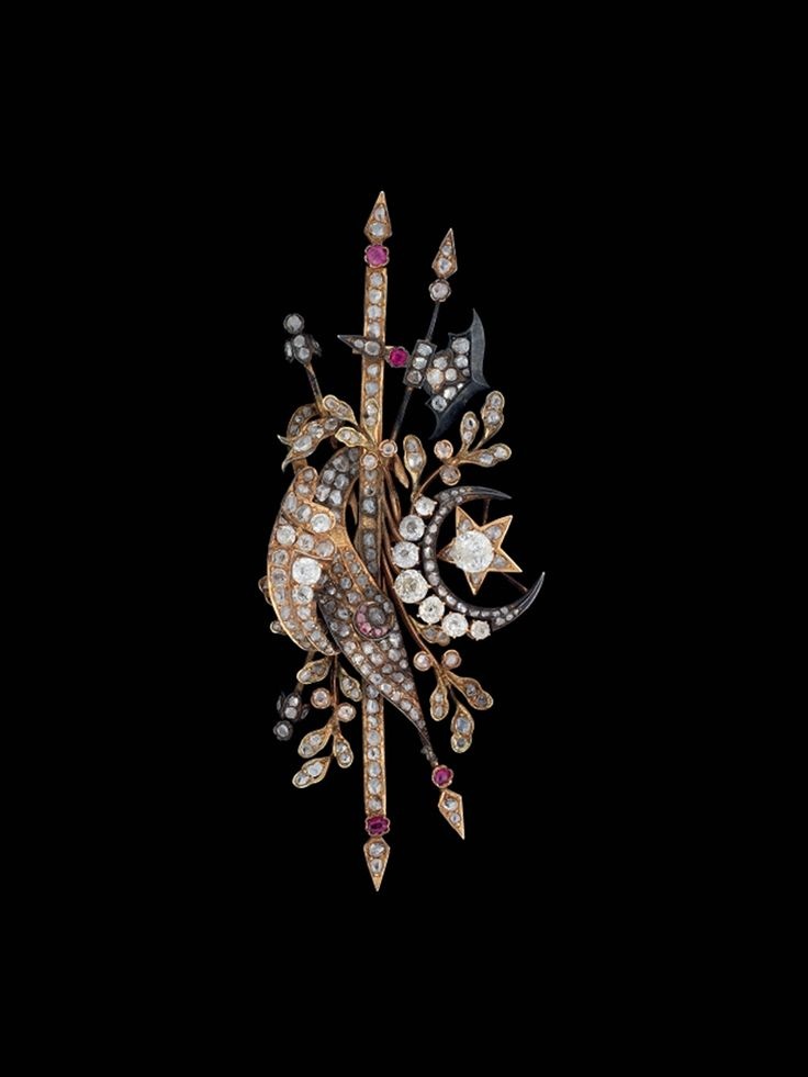 A DIAMOND INSET BROOCH, OTTOMAN TURKEY, 19TH CENTURY, Silver gilt settings with inset diamonds and rubies, formed as a stylised version of the Ottoman coat of arms consisting of the large crescent moon and star along with two flags, one with a pink crescent, representing the flags of the Ottoman dynasty and that of the Islamic Caliphate, set on a base of pointed weapons and scrolling vines, some small areas of rubbing to the gilt surface, with large pin on reverse, 3¾in. (9.7cm.) long