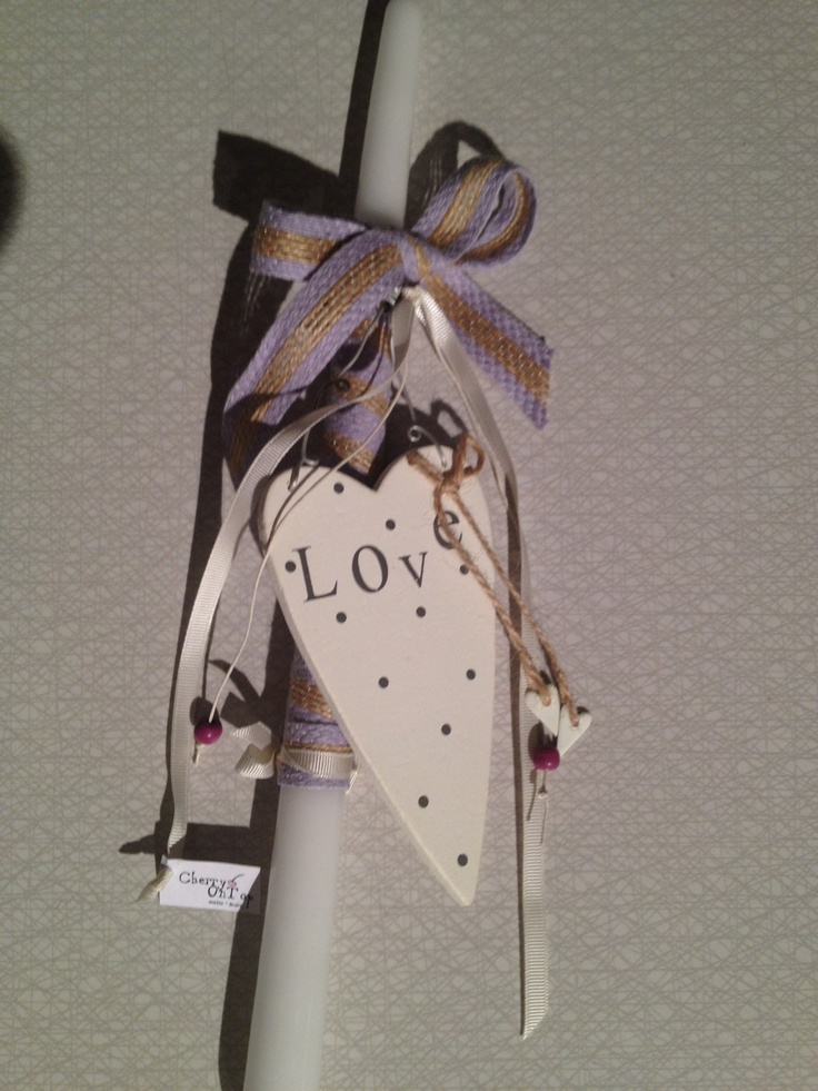 Easter candle with wooden heart decoration and purple linen ribbon