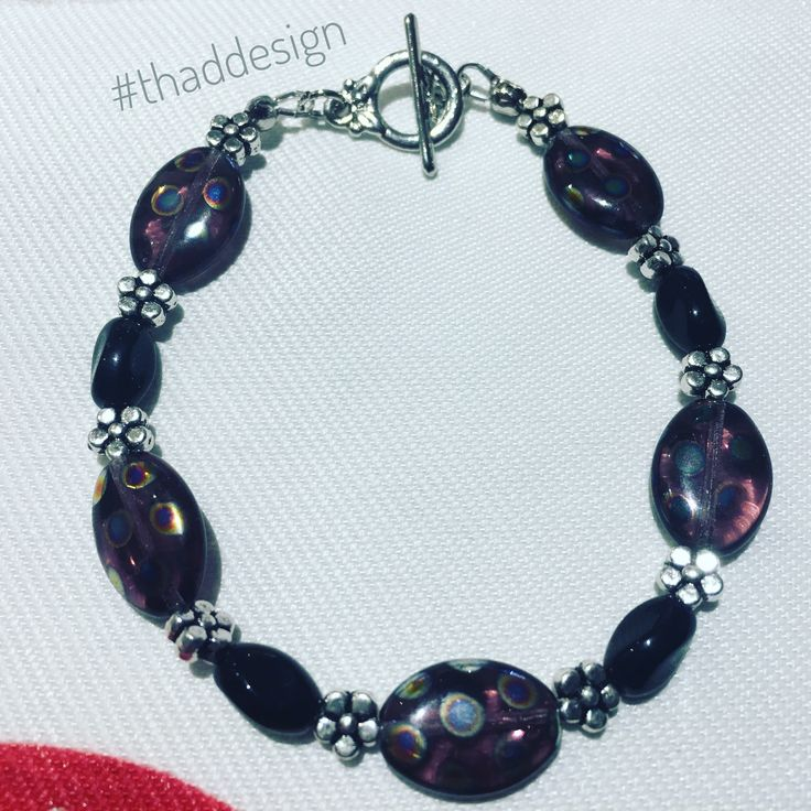 Purple Czech oval glass beads, silver plated flowers and black twisted black beads make up this unique bracelet that is sure to fit any mood.   #bracelet #thaddesign #fashion #bijou