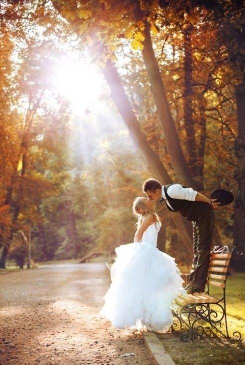 Mariés qui s'embrassent dans un parc aux couleurs de l'automne