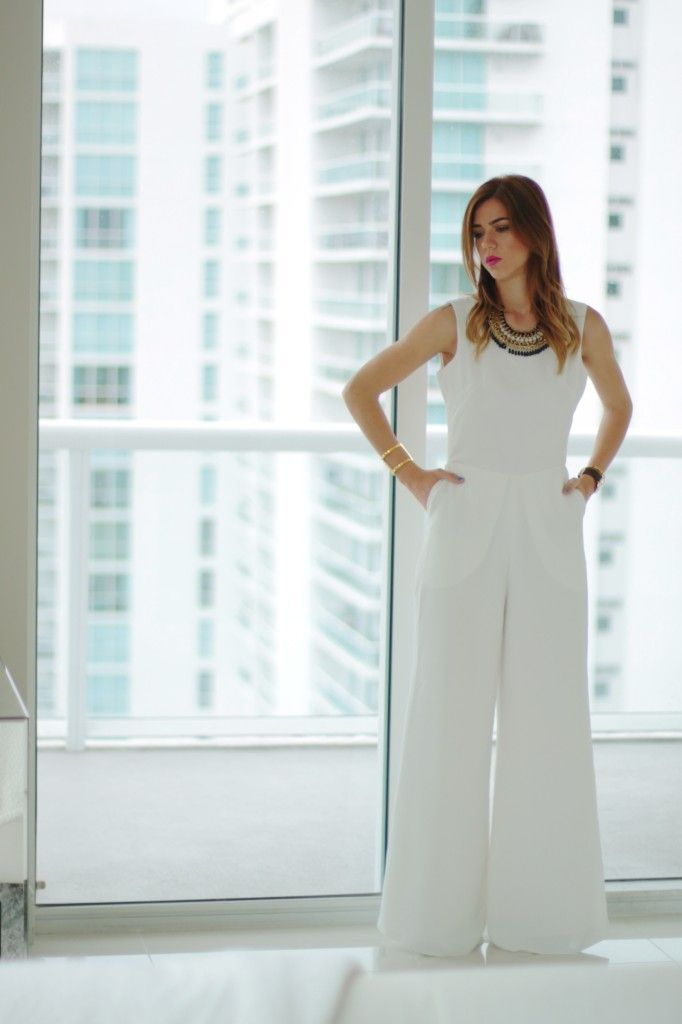 {baring all} An all white jumpsuit, black statement necklace, pop of color urban decay anarchy lip, vince camuto cuff and open back, daniel wellington watch