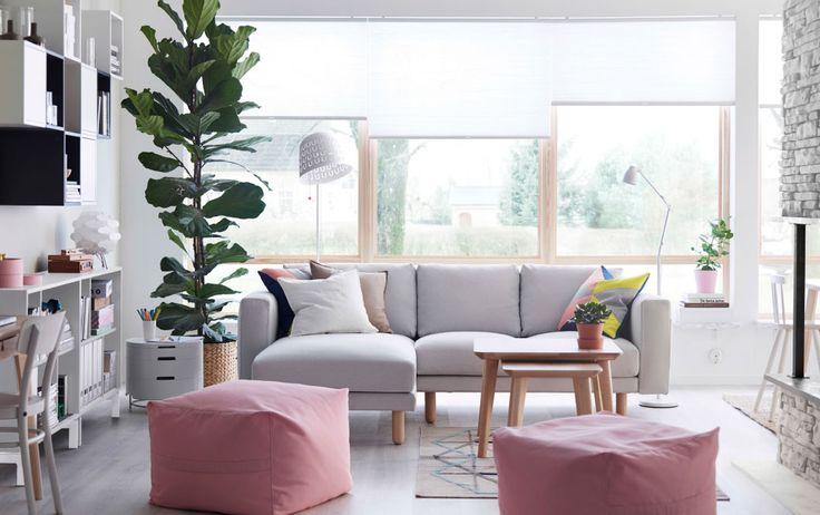 Alegre salón con un sofá de dos plazas blanco con chaise longue, dos pufs con fundas rosas, una mesa de centro y una mesa auxiliar de chapa de fresno.
