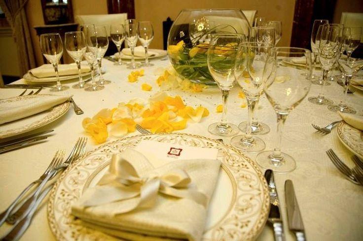 Raffinata mise en place, dai toni dorati, tavolo arricchito da petali sparsi