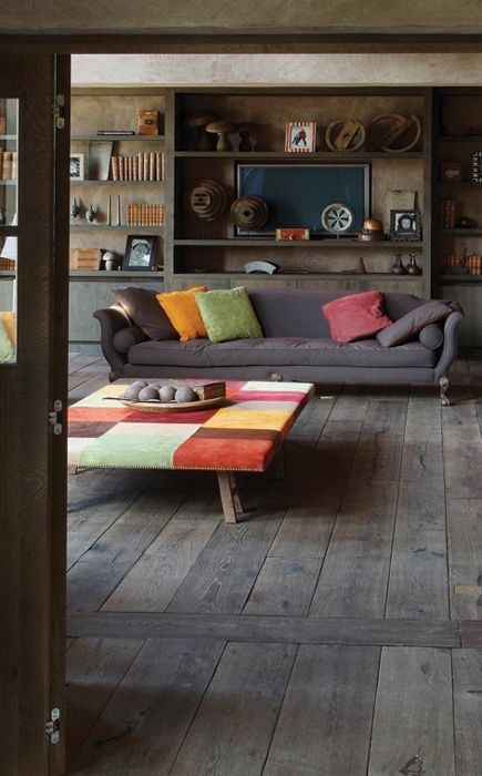 Cleverly decorated room toned down flooring and walls brought to life by multi coloured coffee pouf and cushions.
