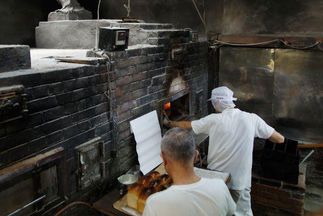 失いたくない、究極の食材「手ごねして、煉瓦窯で焼く山形食パン」 作り手 兵庫県神戸市岡本 フロイン堂竹内善之さん      予約なしではまず買えない山型食パンを目当てに、地元の神戸はもとより、遠方から訪れる顧客も多い「フロイン堂」。ドイツパンの名店「フロインドリーブ」の支店として始まり、以来82年、今でもミキサーなどの機械に頼ることなく、頑なに手作りの味わいを守り続けています。  その理由は「パン作りは、その日の温度や湿度でも、配合や発酵時間などが変わってくるため、マニュアルが作れません。感性で見極めることが必要だから、日々真剣勝負。毎日が素人なんです」。そう語る、現在82歳の2代目の店主・竹内善之さんに習って、3代目となる息子の隆さん、親戚の松本良夫さん、岡山から弟子入りした松浦順二さんの3人も、店奥の工房でパン作りに向き合います。  ◆日本では絶滅寸前の煉瓦のパン窯…