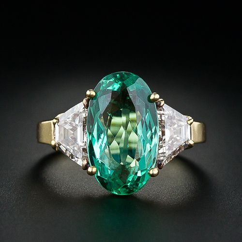 Contemporary rendition of a classic this 18K yellow gold ring features an distinctive oval faceted light green emerald (3.56 carat oval) flanked on each side by trapezoid shaped matched diamonds with a total weight of 1.40 carats (L color, VVS2 clarity).