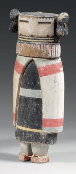 Kachina ANG-CHIN-MANA ou QOCHA-MANA Kachina, HOPI, Arizona, USA Circa 1920 H: 27,7cm Pigments naturels, cottonwood, clous et coton. Le masque blanc finement orné de traits noirs étirés illustrant les yeux, un fin hachurage vertical noir au niveau du front, le masque présente des lignes horizontales de couleur, bleues, jaune et noire en partie inférieure surplombant un relief rectangulaire illustrant une barbe en crin de cheval. Le Kachina porte le costume féminin traditionnel formé d'une…