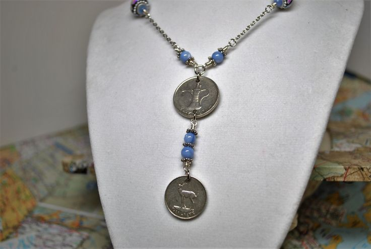 """One 30"""" long silver-plated necklace with wire wrapped stations made with light blue sapphire beads with silver roundels and inlayed mother of pearl large beads.  Then suspended from the light weight cable chain and stations are two coins from the United Arab Emirates.  {Fils and Dirham}  A small lobster clasp is attached.  The necklace can be worn in a shorter length."""