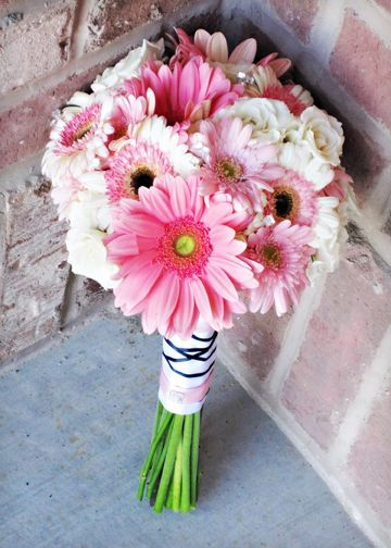Pink, white and black wedding flowers. Pink and white gerbs, (love the black centers) with white spray roses to give the bouquet a better shape. Love the criss-cross ribbon on the handle.