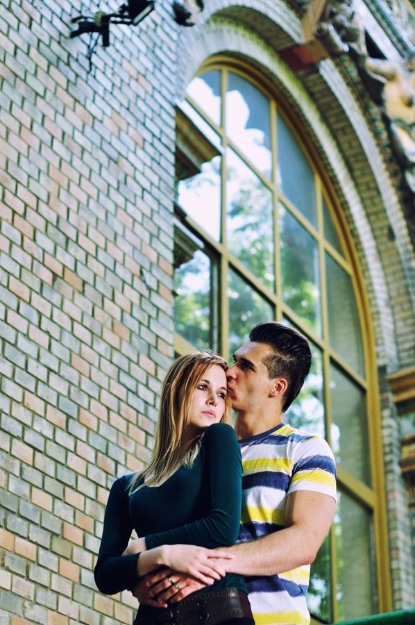 cute young couple in front of a building - kiss on a check