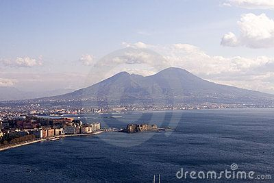 Naples And Mt. Vesuvius From the perspective of the water, the view of the shore line of Naples, Italy, and Mt. Vesuvius in the distance.