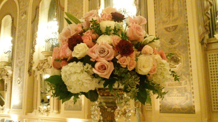 Erika and Mike's centerpiece were designed with luxurious garden roses with blush pink and cream roses and hydrangea with cascading crystals at Hotel duPont.