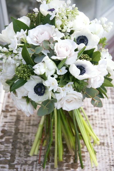 Gorgeous spring inspired wedding bouquet filled with anemones, scented lilac, parrot tulips, skimmia, blush Majolika spray roses and blousy ranunculus.