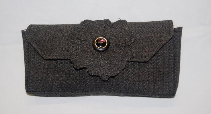 Rozenn – Elegante pochette in tessuto fantasia grigio/nero. Abbellita da un maxi fiore di stoffa completato da un bottone nero e oro,  in corrispondenza della chiusura a calamita di cui è fornita la borsetta. (etc.)   Realizzata interamente a mano. Modello unico