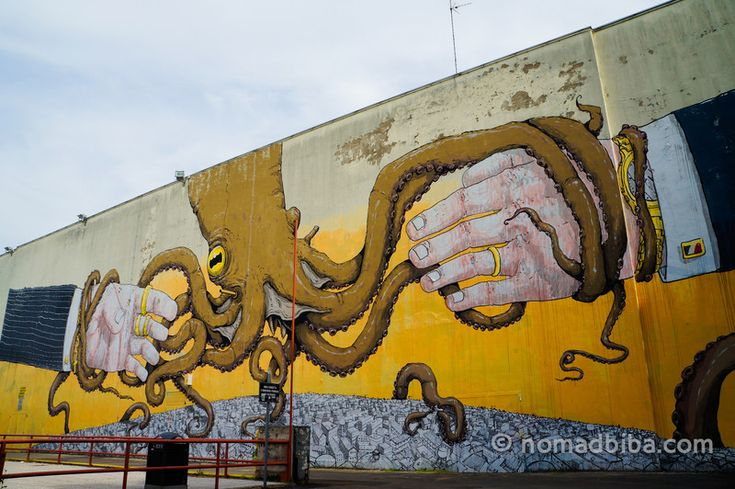 """There was another massive mural on one of the sides of this same building; it features an octopus with its tentacles around a couple of some rich and powerful looking hands. This was another collaboration with fellow Italian artist Ericailcane"" - ""Modena – Street Art"" by @nomadbiba"