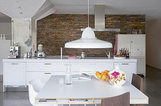 Het keukenblok is aan een kant gezet tegen een van de stoere betonnen steunpilaren die de ruimte rijk is.