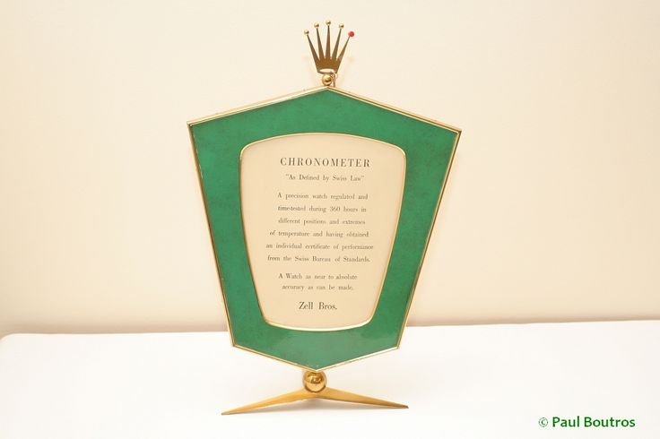 Lot 6: Dealer Advertising Frame, circa 1960 A rather large frame, measuring about 12 inches high, with the legal Swiss definition of Chronometer...adorned with the Rolex coronet at the top.