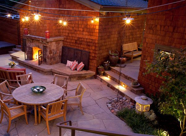 String lights in an inviting backyard deck; outdoor fireplace
