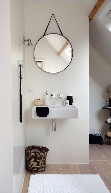 .Moderní koupelna v podkroví, dřevěná podlaha, světlé stěny, zavěšené kulaté zrcadlo, konzolové umyvadlo, proutěný koš na prádlo